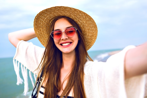 Jovem garota loira feliz fazendo selfie, usando chapéu de palha e óculos de sol bonitos de coração, aproveite as férias de verão perto do oceano. Foto gratuita