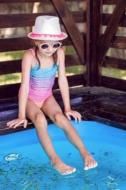 Jovem garota recebendo massagem com peixes pequenos. descascar com peixe. garota desfrutando de procedimento medicinal. massagem nos pés com peixes no aquário closeup. procedimento de spa de peixe. Foto Premium