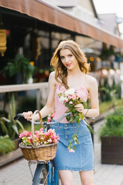 Jovem garota romântica fica e segura uma bicicleta com uma cesta de flores em um verão ensolarado Foto Premium