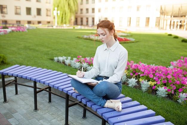 Jovem garota ruiva bonita com sardas sentado em um banco Foto Premium