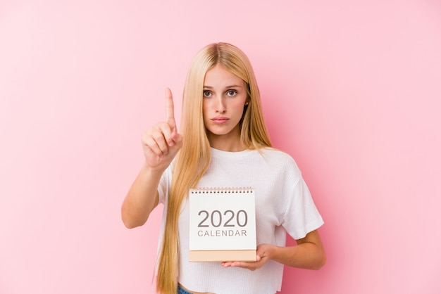 Jovem garota segurando um calendário 2020, mostrando o número um com o dedo. Foto Premium