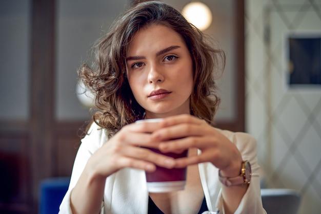 Jovem garota séria tomando café em um café Foto Premium