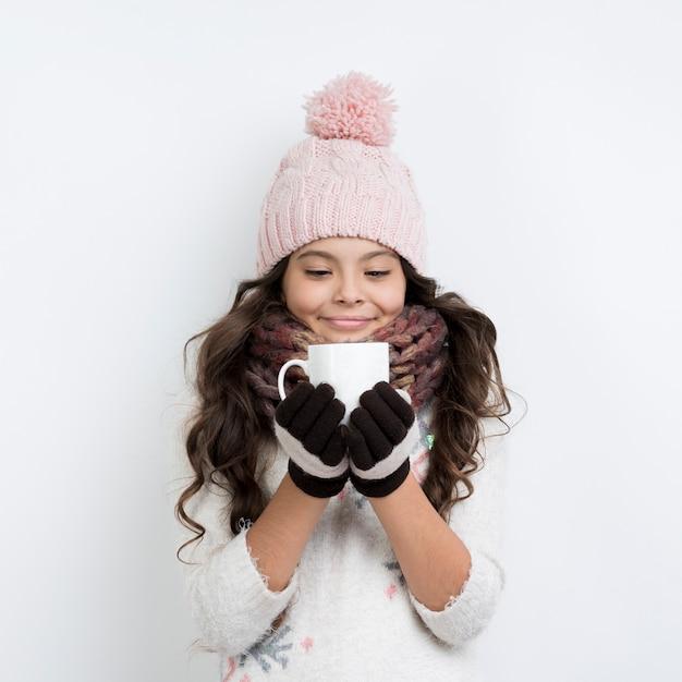 Jovem garota vestindo roupas de inverno e bebendo chá Foto gratuita