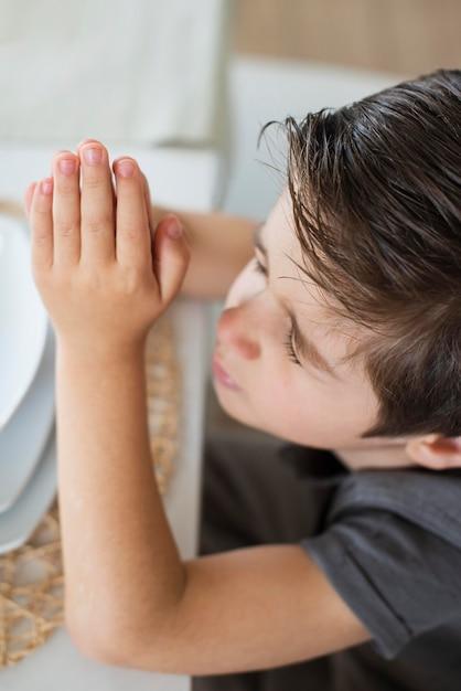 Jovem garoto orando pedindo ajuda Foto gratuita