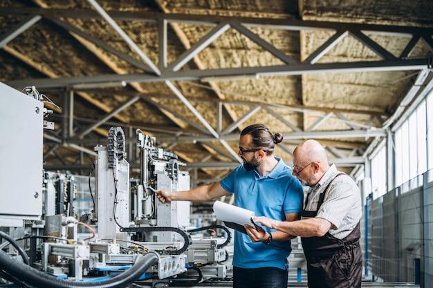 Jovem gerente com barba, mostrando e inspecionando o processo de trabalho do trabalhador profissional adulto na grande fábrica. Foto Premium