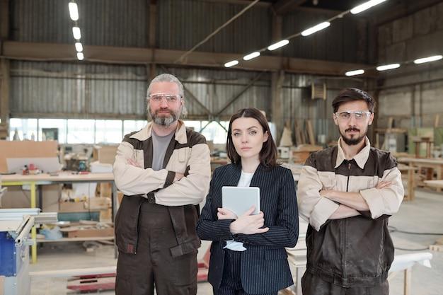 Jovem gerente elegante com touchpad e dois trabalhadores do sexo masculino uniformizados, cruzando os braços no peito, enquanto se posicionam em fila contra o interior da oficina Foto Premium