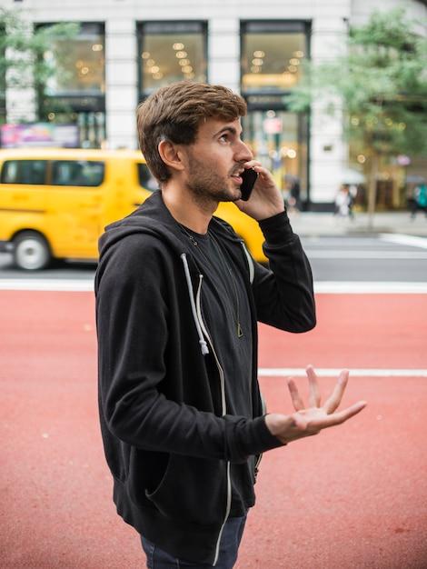 Jovem, gesticulando enquanto fala no smartphone Foto gratuita