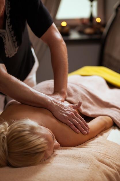 Jovem gosta de massagem em um spa Foto gratuita