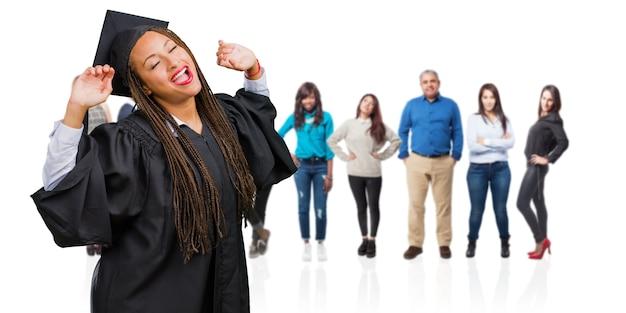 Jovem, graduado, mulher preta, desgastar, tranças, escutar música, dançar, e, tendo divertimento Foto Premium