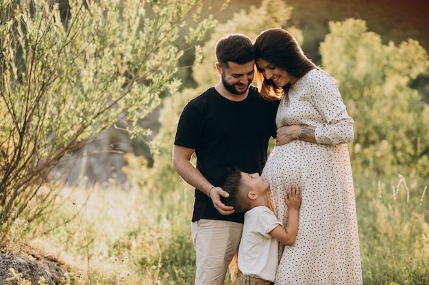 Jovem grávida com marido e filho em uma floresta Foto gratuita