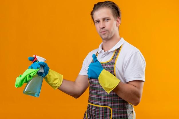 Jovem hansdome usando avental e luvas de borracha segurando um spray de limpeza e tapete com um sorriso confiante no rosto mostrando polegares em pé sobre a parede laranja Foto gratuita