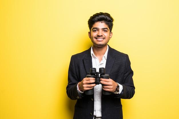 Jovem hindu com binóculos isolado na parede amarela Foto gratuita