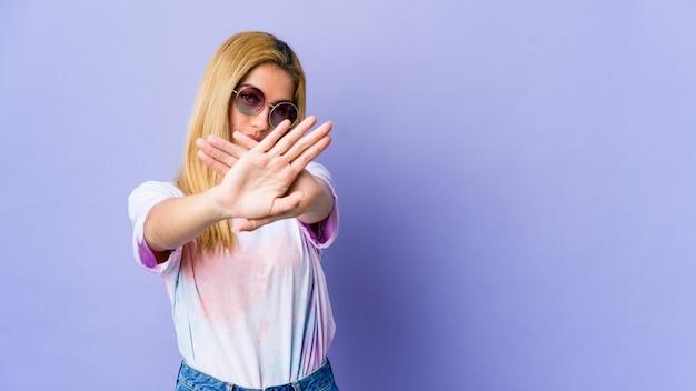 Jovem hippie de óculos fazendo um gesto de negação Foto Premium