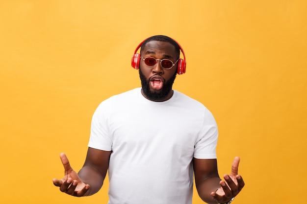 Jovem, homem americano africano, desgastar, headphone, e, apreciar, música, sobre, ouro amarelo, fundo Foto Premium