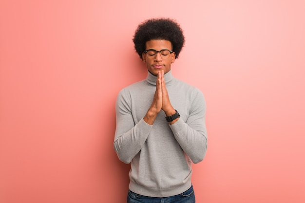 Jovem, homem americano africano, sobre, um, parede cor-de-rosa, orando, muito, feliz, e, confiante Foto Premium