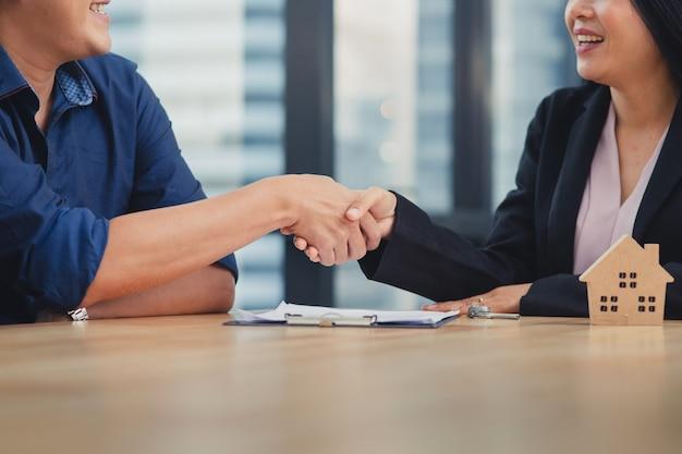 Jovem homem asiático fazendo contrato com a agência de venda de casa imobiliária, agente feminina, apertando a mão com homem caucasiano para obter a chave do contrato e casa Foto Premium