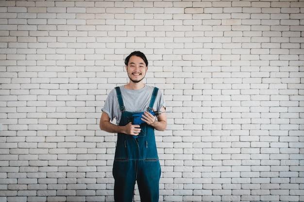 Jovem, homem asiático, segurando, broca poder, ficar, frente, parede branca tijolo, sorrindo Foto Premium