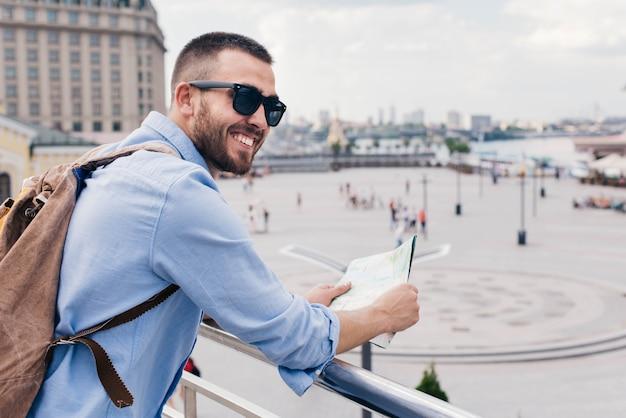 Jovem homem barbudo carregando mochila e segurando o mapa em pé perto de trilhos Foto gratuita