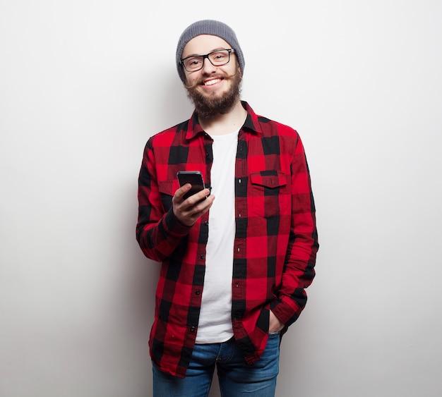 Jovem homem barbudo com telefone móvel Foto Premium