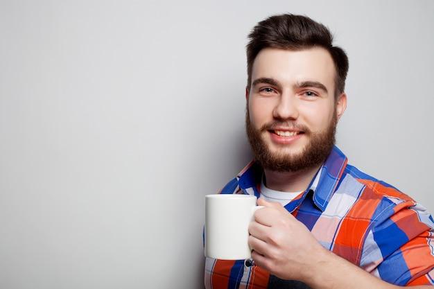 Jovem homem barbudo com uma xícara de café Foto Premium