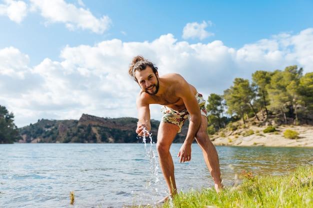 Jovem homem barbudo descansando no lago Foto gratuita