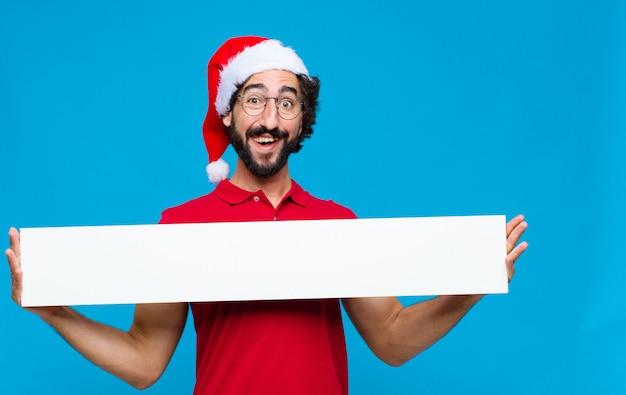 Jovem homem barbudo louco com chapéu de papai noel. conceito de natal Foto Premium