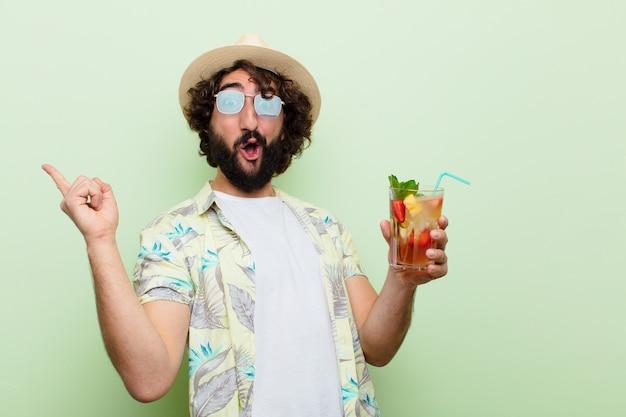Jovem homem barbudo louco com um cocktail. conceito de turista Foto Premium