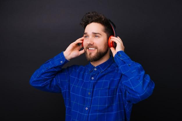 Jovem homem barbudo olhando de lado um ouvir a música através de um fone de ouvido vermelho sobre fundo preto. Foto Premium