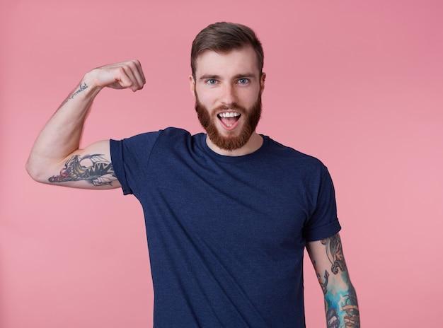 Jovem homem bonito de barba ruiva demonstra bíceps e força com a boca bem aberta, olhando para a câmera isolada sobre fundo rosa. Foto gratuita