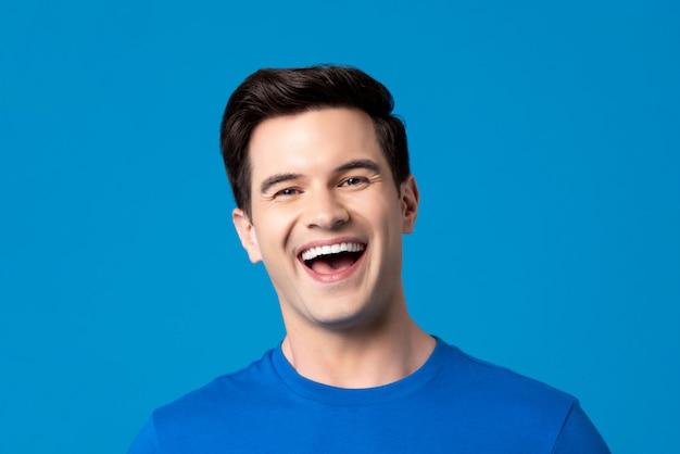 Jovem homem caucasiano amigável em riso de t-shirt azul liso Foto Premium