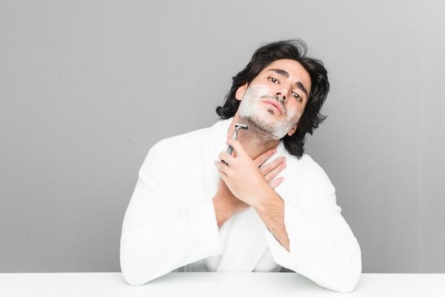 Jovem homem caucasiano barbear sua barba isolada em uma parede cinza Foto Premium