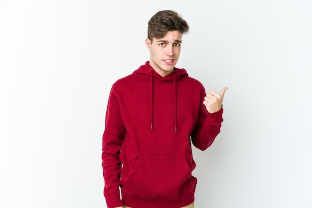 Jovem homem caucasiano chocado apontando com o dedo indicador para um espaço de cópia. Foto Premium