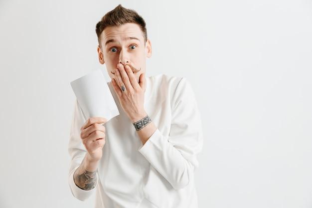 Jovem homem caucasiano com uma expressão de felicidade e surpresa ganhou uma aposta no espaço cinza Foto gratuita