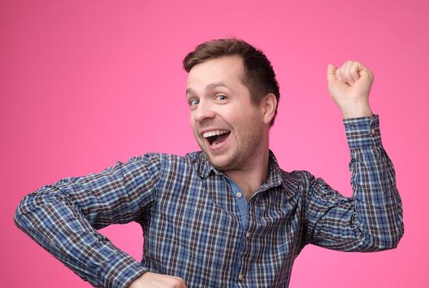 Jovem homem caucasiano dançando sobre fundo rosa Foto Premium