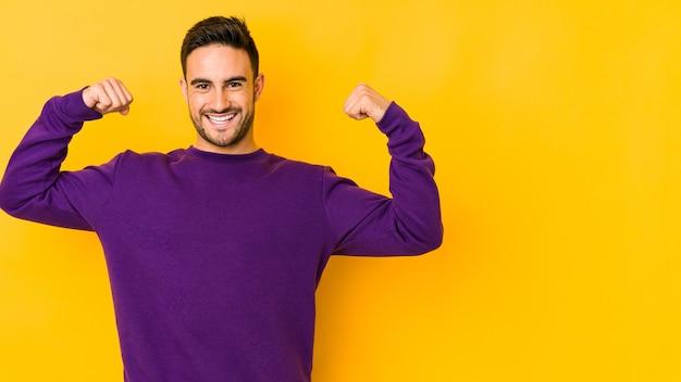 Jovem homem caucasiano isolado em amarelo mostrando força gesto com os braços, símbolo do poder feminino Foto Premium