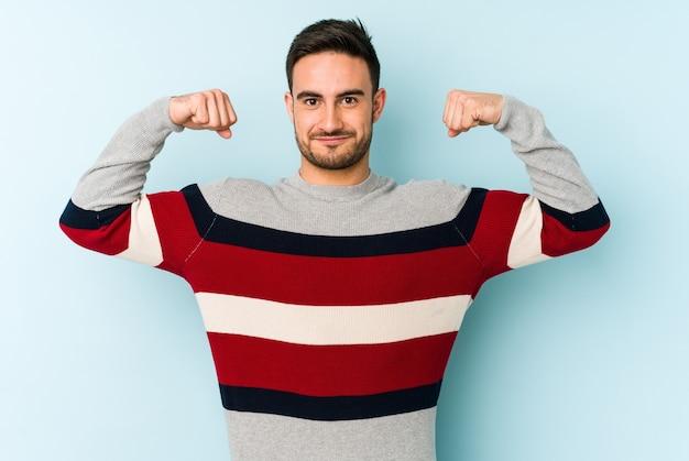 Jovem homem caucasiano isolado em azul mostrando força gesto com os braços, símbolo do poder feminino Foto Premium