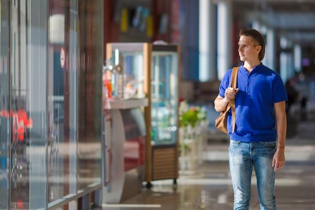 Jovem homem caucasiano no aeroporto interior à espera de embarque Foto Premium