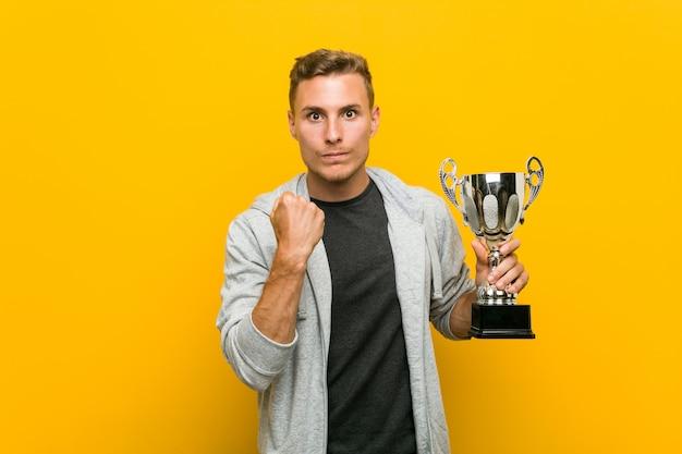 Jovem homem caucasiano segurando um troféu, mostrando o punho para a câmera, expressão facial agressiva. Foto Premium