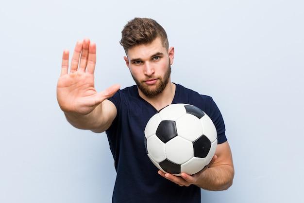 Jovem homem caucasiano segurando uma bola de futebol em pé com a mão estendida, mostrando o sinal de stop, impedindo-o. Foto Premium