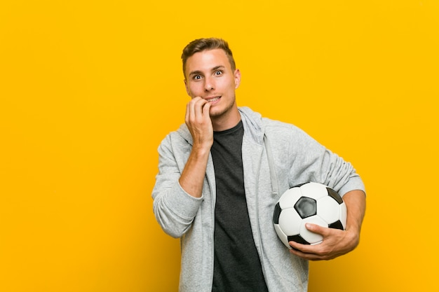 Jovem homem caucasiano segurando uma bola de futebol, roer as unhas, nervoso e muito ansioso. Foto Premium