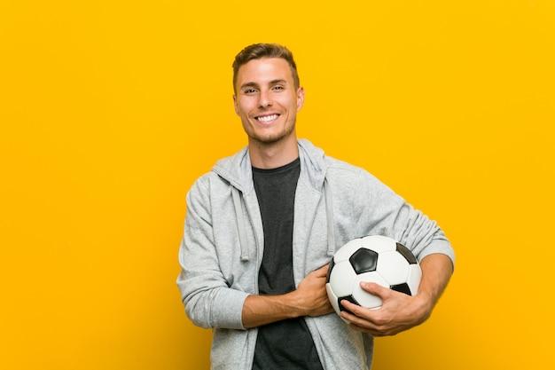 Jovem homem caucasiano segurando uma bola de futebol sorrindo confiante com braços cruzados. Foto Premium