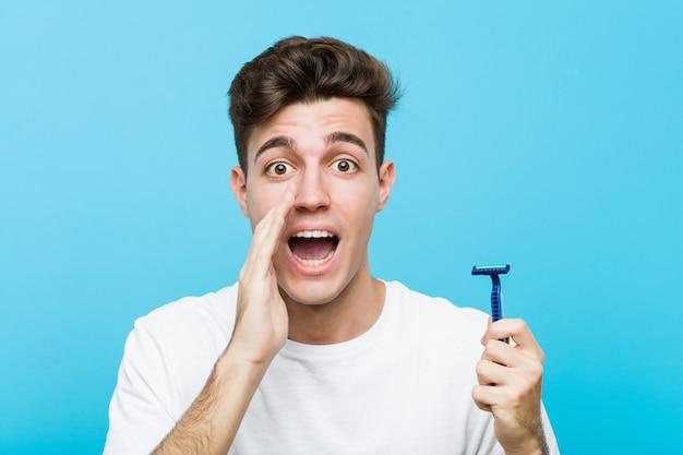 Jovem homem caucasiano segurando uma lâmina de barbear gritando animado para a frente. Foto Premium