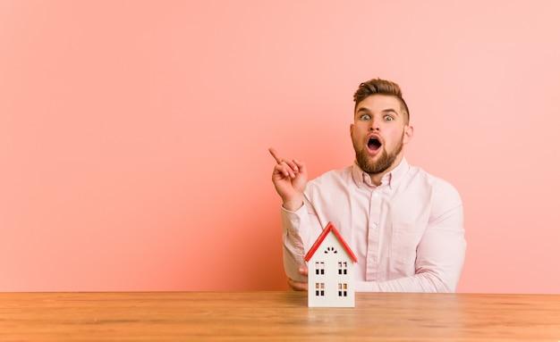 Jovem homem caucasiano sentado com um ícone de casa, tendo uma ótima idéia Foto Premium