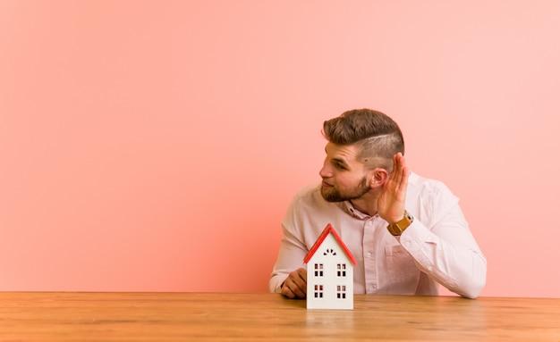 Jovem homem caucasiano sentado com um ícone de casa tentando ouvir uma fofoca. Foto Premium