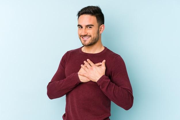 Jovem homem caucasiano tem uma expressão amigável, pressionando a palma da mão no peito. conceito de amor. Foto Premium