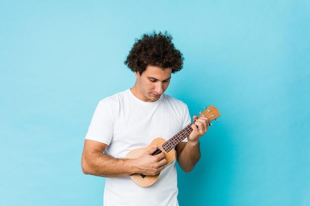 Jovem homem caucasiano tocando ukelele feliz isolado Foto Premium