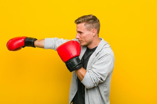 Jovem homem caucasiano vestindo uma luvas de boxe Foto Premium