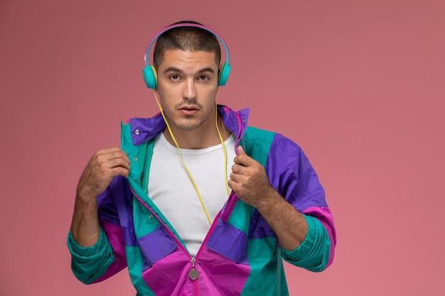 Jovem homem com casaco colorido posando e ouvindo música no fundo rosa Foto gratuita