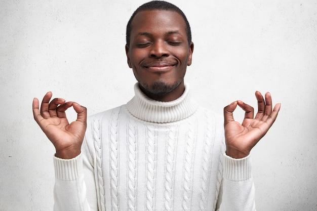 Jovem homem contente de pele escura mantém os olhos fechados e os dedos em sinal de mudra, tem uma expressão calma, tenta relaxar após um dia cansativo Foto gratuita