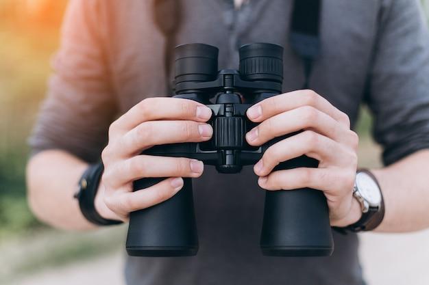 Jovem homem de aventura viajando segurando binóculos nas mãos Foto Premium